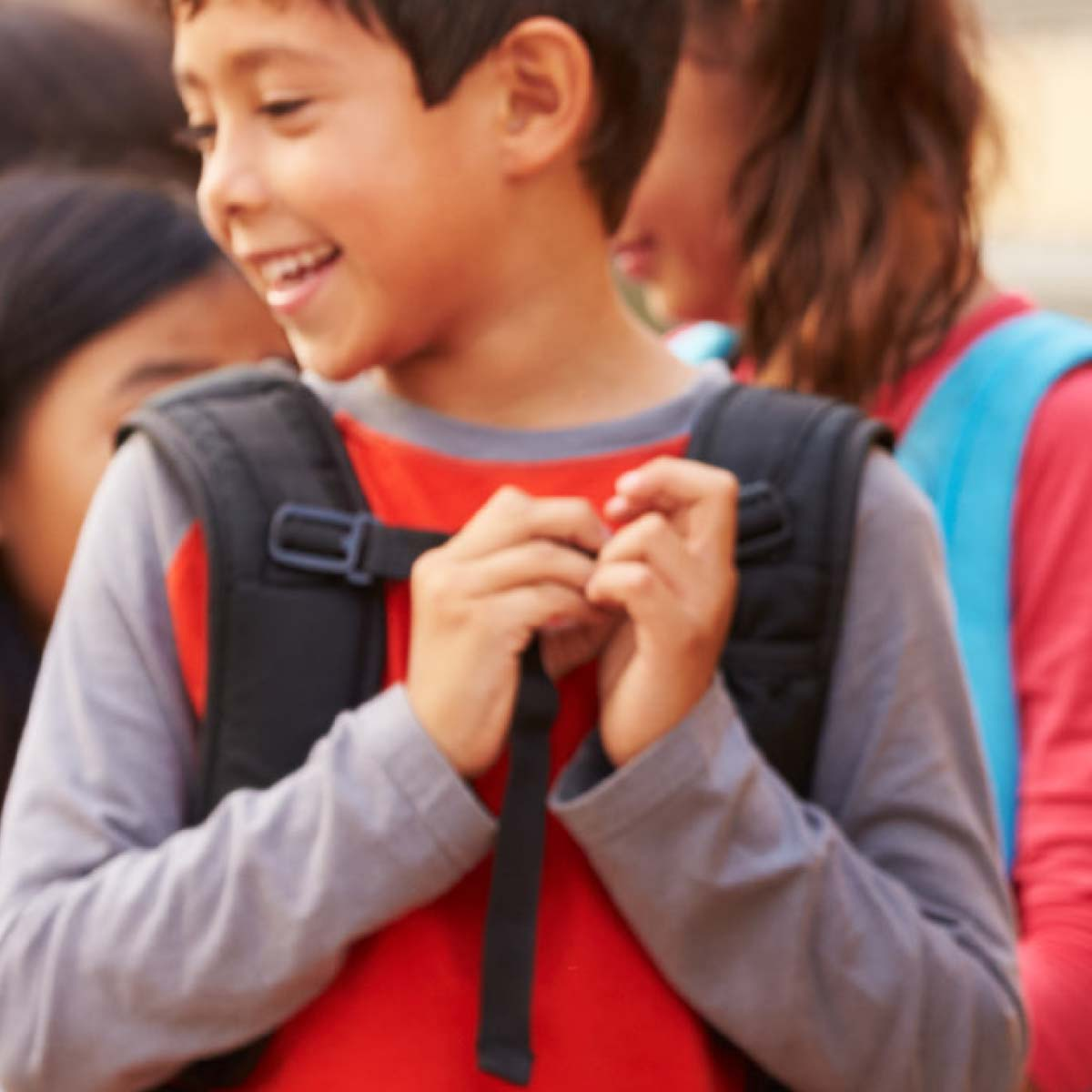 Children with backpacks entering school