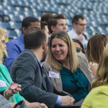 Professionals networking at sporting event.