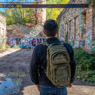 student with backpack overlooking graffiti in alley