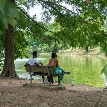 couple sitting on park bench looking at river